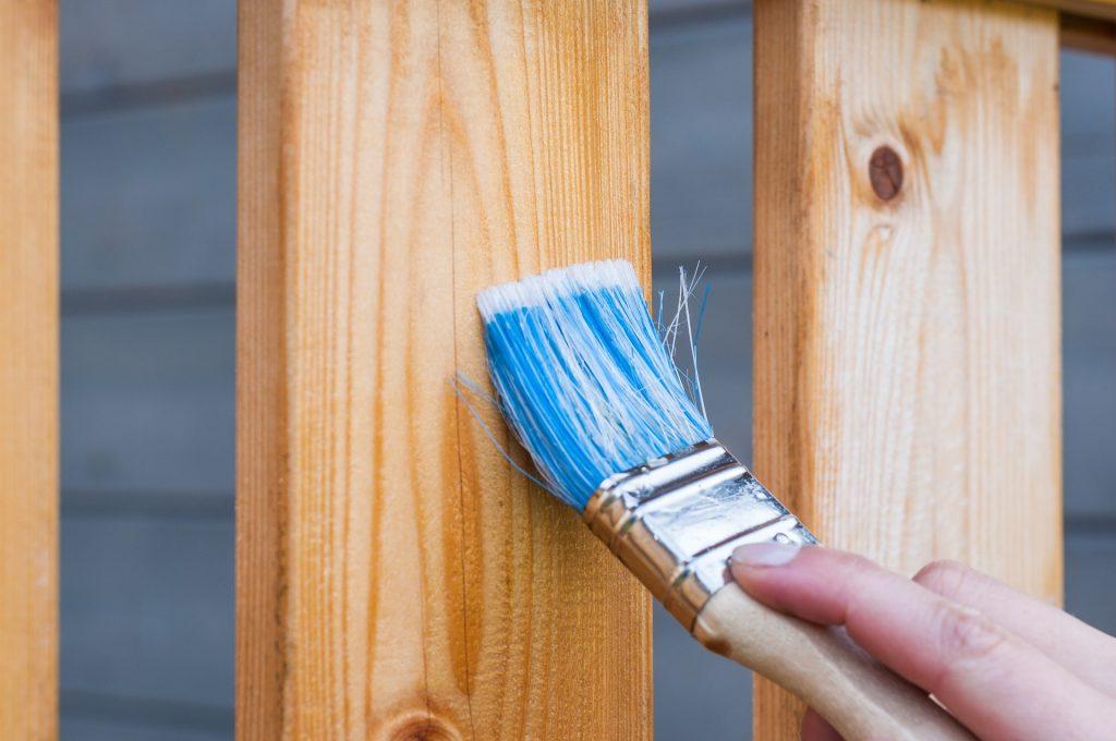 Des travaux de peintruee sur bois avec un pinceau