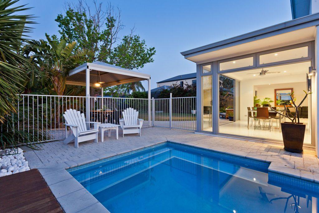 Une piscine devant une maison contemporaine avec un bassin géométrique