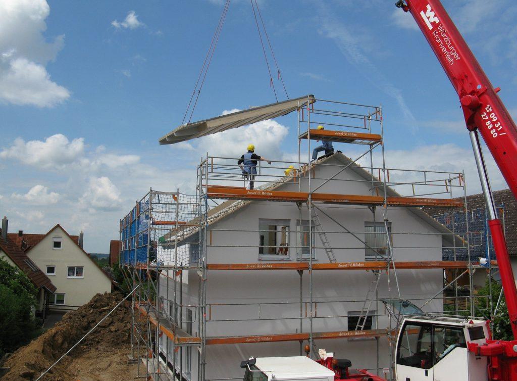 Un maison en construction avec un camion grue et installation de toiture