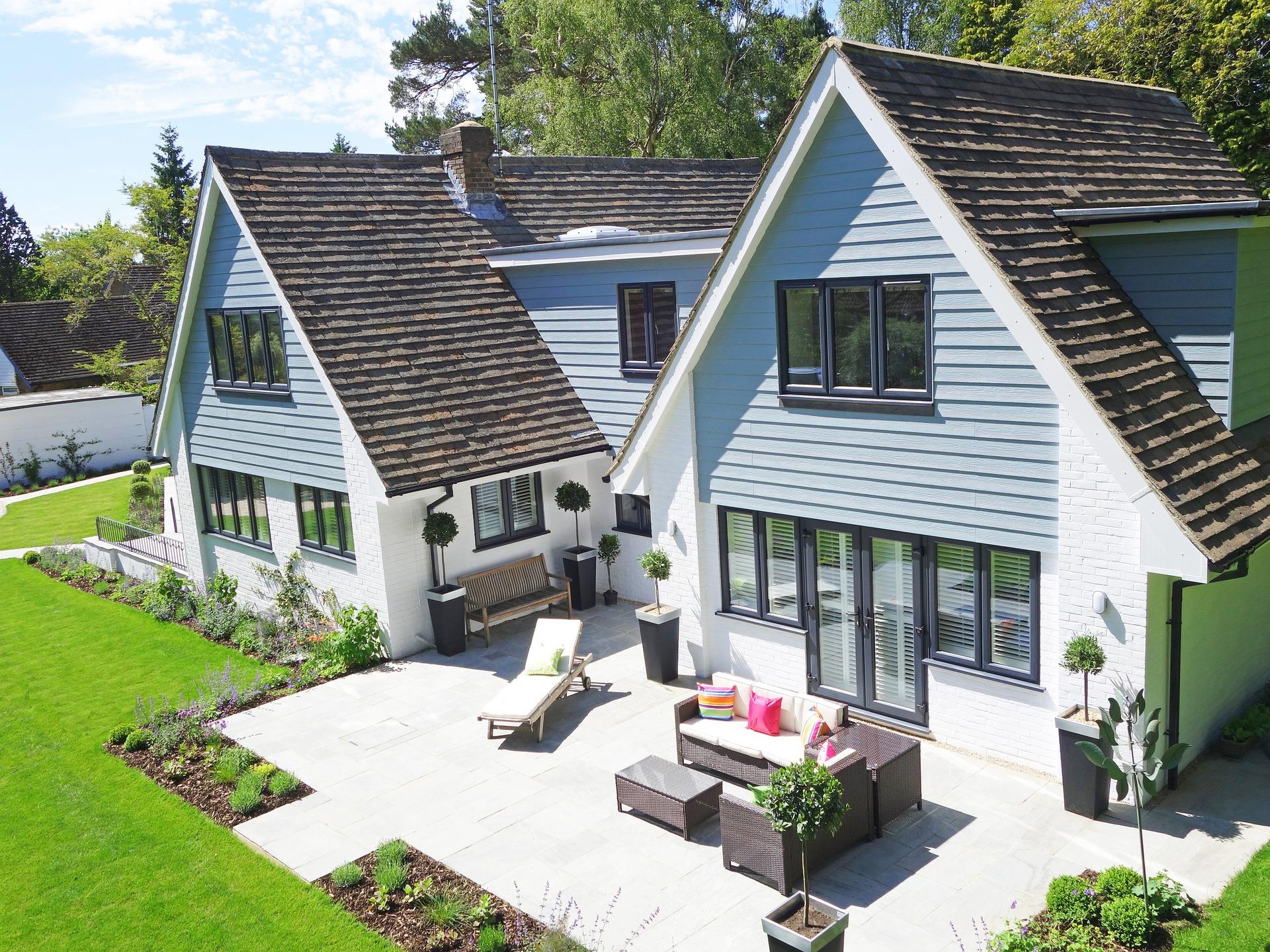 Une maison bleue avec une belle terrasse et un jardin