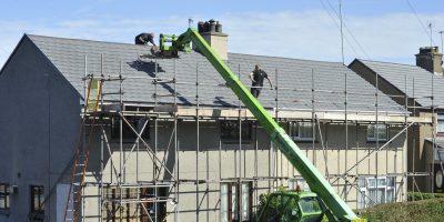 Travaux toit maison avec grue verte