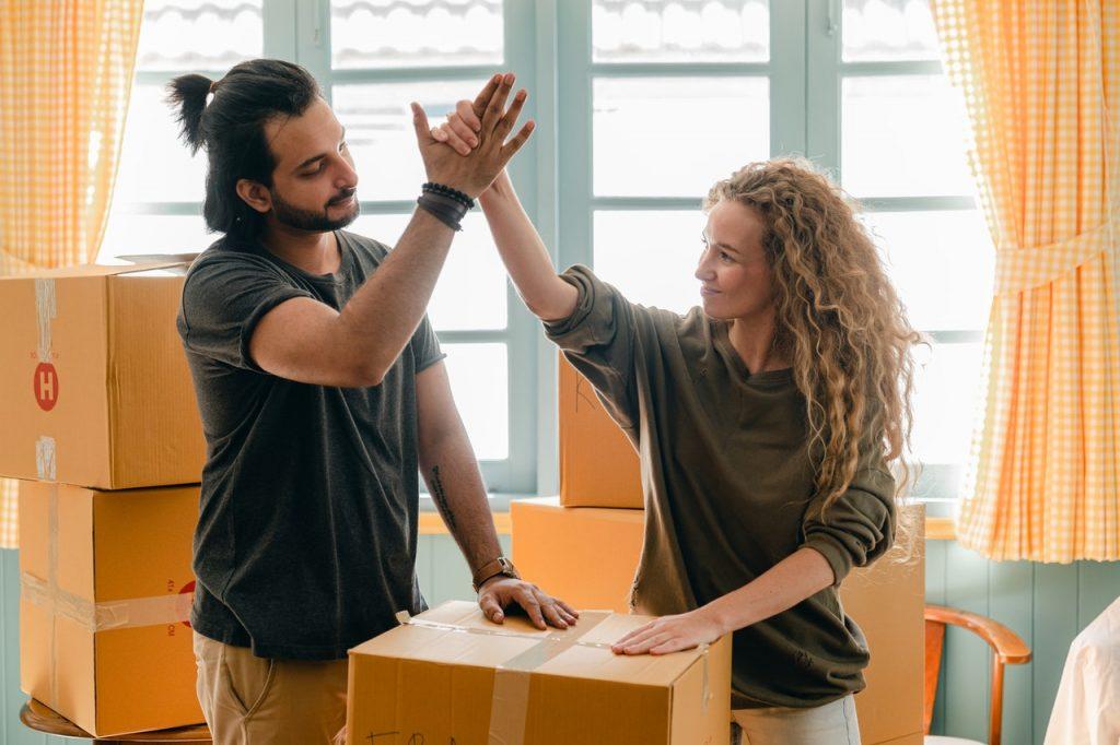 deux personnes au milieu de cartons qui se tapent dans la main